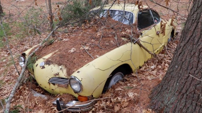 A old Volkswagen Karman Ghia left in the woods